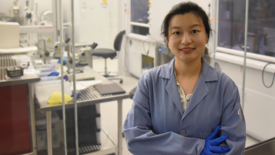 Xiaoyue Ni wearing blue lab coat in her lab