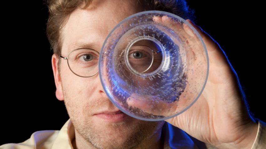 man looking through glass cylinder